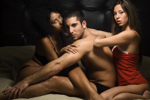 Man and Two Women in Bed Together --- Image by © Ben Welsh/zefa/Corbis